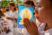 20 OCTOBER 2012 - BANGKOK, THAILAND:  A woman holds a Buddhist prayer card and prays at a special alms giving ceremony in Bangkok. More than 2,600 Buddhist Monks from across Bangkok and thousands of devout Thai Buddhists attended the mass alms giving ceremony in Benjasiri Park in Bangkok Saturday morning. The ceremony was to raise food and cash donations for Buddhist temples in Thailand's violence plagued southern provinces. Because of an ongoing long running insurgency by Muslim separatists many Buddhist monks in Pattani, Narathiwat and Yala, Thailand's three Muslim majority provinces, can't leave their temples without military escorts. Monks have been targeted by Muslim extremists because, in the view of the extremists, they represent the Thai state.       PHOTO BY JACK KURTZ