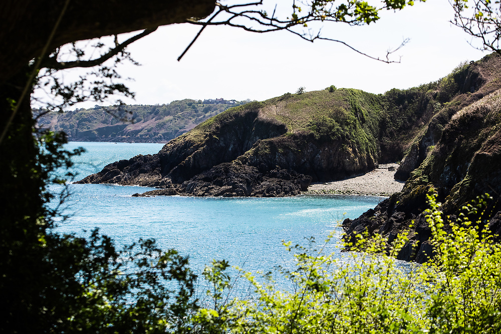 Vicard Harbour - a small hidden pebbly cove, surrounded by calm blue sea and cliffs on the north coast of Jersey, CI