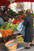 Vegetables and fruits for sale at a market stall at the street market in Bergerac, carrots lettuce and other. A woman in black shopping. Bergerac Dordogne France