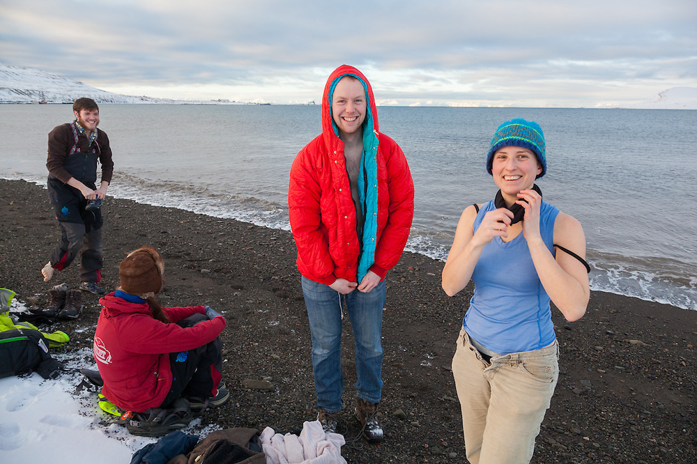 Nate Stevens (l-r), Alistair Everett, and Désirée Treichler get undressed on the beach in Longyearbyen, Svalbard for a dip into Adventfjorden. Heidi Lindebotten sits it out.