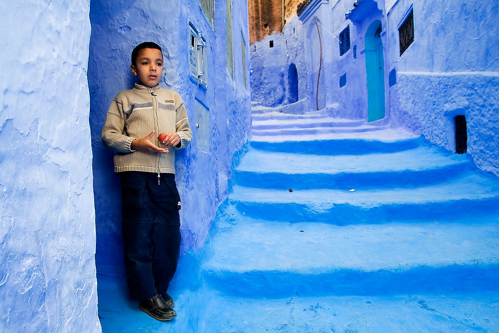 A young boy stands alone holding a red top in a blue alleyway in Chefchaouen medina, Morocco.