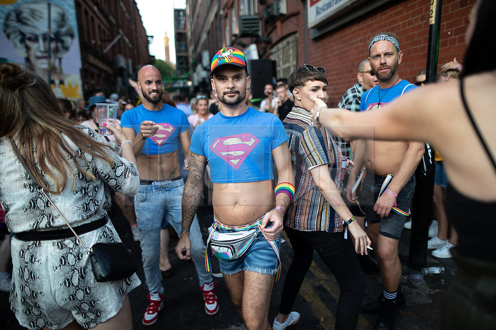 © Licensed to London News Pictures . 25/08/2019. Manchester, UK. Three men wearing crop top Superman t-shirts outside the Molly House pub . Revellers in Manchester's Gay Village during the city's annual Gay Pride festival , which celebrates LGBTQ+ life and is the largest of its type in Europe . Photo credit: Joel Goodman/LNP
