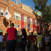Fans gather outside Fenway Park before a summer evening game .