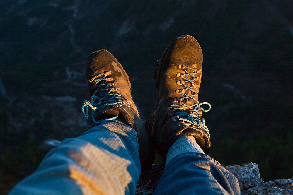 Ethan Welty dangles his boots over the edge of a cliff at sunset in the Diois, Drôme Valley, France.