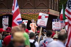 "© Licensed to London News Pictures. 14/07/2018. London, UK. An inflatable sex doll with the face of London Mayor Sadiq Khan is head aloft . Supporters of US President Donald Trump and EDL founder Tommy Robinson ( real name Stephen Yaxley-Lennon ) hold a "" Welcome Trump "" demonstration opposite the American Embassy . Trump is currently in Scotland and Robinson is in HMP Hull . Photo credit: Joel Goodman/LNP"
