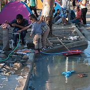 An Afghan refugee is washing himself in Kara Tepe camp.
