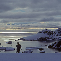 A ski mountaineer takes pictures of Gerlache Strait from the Calley Glacier on the Antarctic Peninsula, Antarctica.