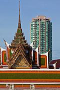 09 JULY 2011 - BANGKOK, THAILAND: A condominium development on the Chao Phraya River sits behind a large Buddhist temple in Bangkok, Thailand.   PHOTO BY JACK KURTZ
