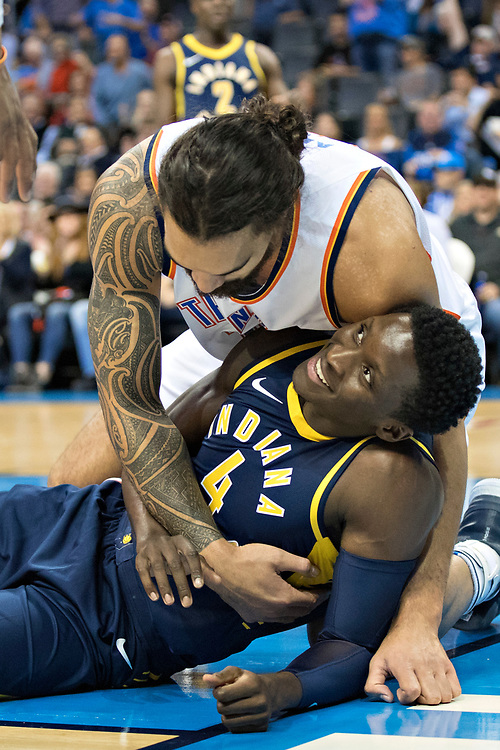 OKLAHOMA CITY, OK - OCTOBER 25:  Steven Adams #12 of the Oklahoma City Thunder helps up Victor Oladipo #4 of the Indiana Pacers at the Chesapeake Energy Arena on October 25, 2017 in Oklahoma City, Oklahoma.  NOTE TO USER: User expressly acknowledges and agrees that, by downloading and or using this photograph, User is consenting to the terms and conditions of the Getty Images License Agreement.  The Thunder defeated the Pacers 114-96.  (Photo by Wesley Hitt/Getty Images) *** Local Caption *** Steven Adams; Victor Oladipo