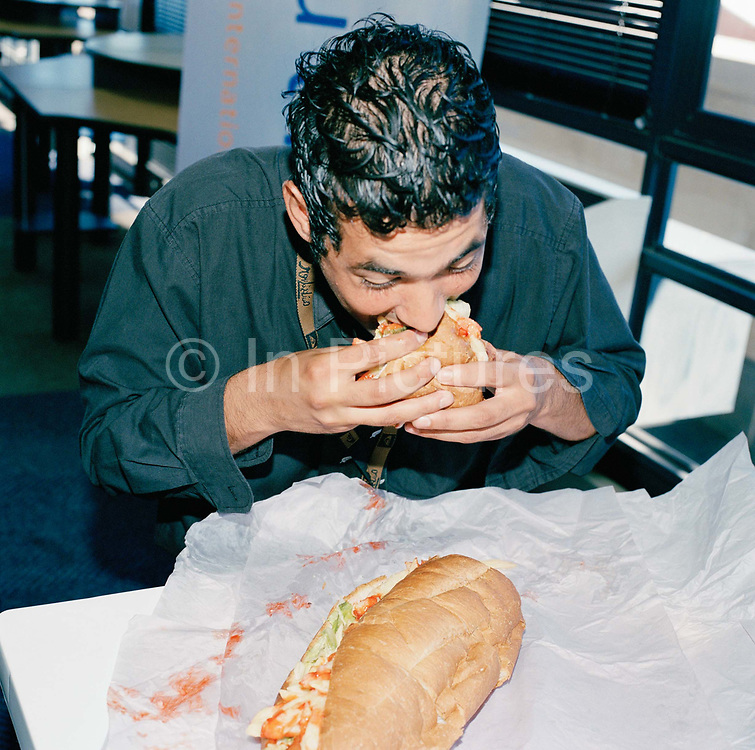 Nur de Bruyn team leader, enjoying Lunch time at a call centre in Capetown, South Africa. This  extremely large chip sandwich is normally shared. From the series Desk Job, a project which explores globalisation through office life around the World.
