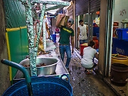 03 FEBRUARY 2015 - BANGKOK, THAILAND: A man carries a box down a soi (alley) in the Chinatown section of Bangkok. After months of relative calm following the May 2014 coup, tensions are increasing in Bangkok. The military backed junta has threatened to crack down on anyone who opposes the government. Relations with the United States have deteriorated after Daniel Russel, the US Assistant Secretary of State for Asian and Pacific Affairs, said that normalization of relations between Thailand and the US would depend on the restoration of a credible democratically elected government in Thailand.   PHOTO BY JACK KURTZ