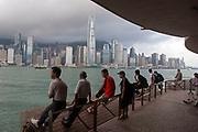 Workers wait for a boat that will pick them up for their days work in Kowloon, Hong Kong, China. At approximately 6am workers start to gather here near the Star Ferry terminal. The Hong Kong skyline, dominated by the Bank of China building towers over Hong Kong Harbour in the morning light.