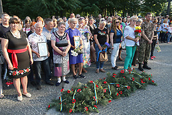 June 14, 2018 - Dnipro, Ukraine - Attendees stay by a garland during a commemorative event in memory of the perished soldiers killed in the Il-76 military plane crash on the Remembrance Alley for ATO Soldiers and the Heavenly Hundred Heroes on the fourth anniversary of the tragedy, Dnipro, central Ukraine, June 14, 2018. On June 14, 2014, the aircraft was shot down by the separatists near the Luhansk airport in eastern Ukraine claiming the lives of 40 soldiers of the 25th Separate Airborne Brigade and nine crew members on board. Ukrinform. (Credit Image: © Mykola Miakshykov/Ukrinform via ZUMA Wire)
