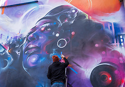 © Licensed to London News Pictures;02/04/2021; Bristol, UK. Artist Mr Cenz works on a giant mural of Jen Reid, the woman who stood on the plinth of the statue of Edward Colston after it was torn down at a Black Lives Matter protest in Bristol in 2020 and of whom a statue was made and temporarily placed on the plinth. The mural is on the wall by The Canteen on Stokes Croft, and replaces an earlier mural of Breakdancing Jesus. Bristol street artist Inkie is contributing text to the mural. Photo credit: Simon Chapman/LNP.
