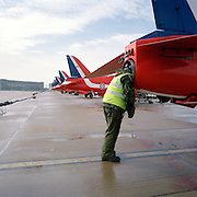 Wearing ear-defenders,military green camouflage and fluorescent tabard, a 'line' engineer from the elite 'Red Arrows', Britain's prestigious Royal Air Force aerobatic team, inserts his head into the jet pipe of a Hawk aircraft immediately after a winter training flight at the team's headquarters at a damp RAF Scampton, Lincolnshire. The man is a member of the team's support ground crew (called the Blues because of their distinctive blue overalls worn at summer air shows). Checking for irregular blemishes within the aircraft's exhaust is a vital aspect of maintenance jets whose engines need to perform as the highest level, especially if its performance, and that of each pilot's manoeuvres need to be perfect. Power reduction can ruin a display for tens of thousands of spectators but an engine failure could be catastrophic..