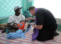 Father John Vien (right) of St. Louis, Missouri, administers ashes to Jacque Delvi, 3, as his mother Chela Michelle cradles him in the temporary pediatric ward in Milot, Haiti, on Ash Wednesday February 17, 2010.