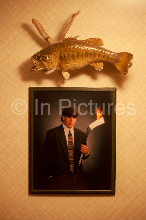 Hunter Byron Grubbs home is full of the guns, trophies, stuffed animals and hunting paraphernalia of an experienced hunter, near Minot, North Dakota, United States. Here, in his basement, a prized stuffed trout is mounted above a photograph of his son, a fine ice hockey player.