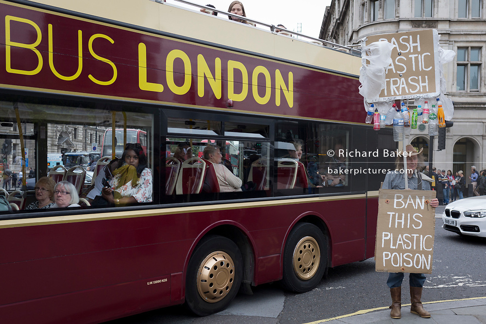 A plastics protestor stands on the corner of Parliament Square as a passing tour bus drives past in Westminster, on 18th June 2019, in London, England.