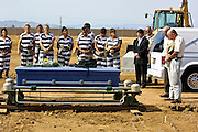"""05 JULY 2001 -- PHOENIX, AZ:  Members of the women chain gang in Maricopa County, Phoenix, AZ, bury a homeless person in the county's """"Potter's Field"""" or cemetery for the indigent. Maricopa county sheriff Joe Arpaio claims to have the only women's chain gang in the United States. He has been criticized for the chain gang but claims to be an """"equal opportunity incarcerator."""" He has said that if puts men on a chain gang he will also put women on a chain gang. The women are prisoners in the county jail and volunteer for duty on the chain gang because it gets them out of the jail for six hours a day. The chain gang also buries the county's homeless and indigents. PHOTO BY JACK KURTZ"""