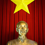 A golden statue of Ho Chi Minh, the founding leader of modern Communist Vietnam, with the Vietnamese star against deep red drapes on display in Reunification Palace in Ho Chi Minh City (Saigon), Vietnam.