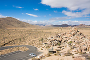 A single car is parked in an empty parking lot at Hidden Valley in Joshua Tree National Park, California.