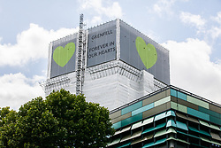 London, UK. 14th June, 2018. Green Grenfell hearts are now positioned at the top of the Grenfell Tower on all sides.