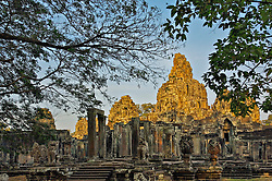 Last rays of sunlight illuminating tops of west side of Bayon temple, seen through tress, with entrance columns in shadow but clearly visible