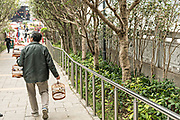 A Chinese man strolls through the Yuen Po Street Bird Garden with his caged songbirds in Mong Kok, Kowloon, Hong Kong.