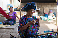 """Margarita """"Abuelita"""" Perez, creates a bracelet which will be sold to tourists in Panajachel. The women of the Perez family work together to create clothing, jewelry and other textiles to support themselves."""