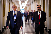 President Donald Trump walks down the hall of the United States Treasury with Treasury Secretary Steven Mnuchin for the signing of one executive order and two presidential memoranda on tax and Wall Street regulations in Washington, District of Columbia, U.S., on Friday, April 21, 2017. This was President Trump's first visit to the Treasury Department.