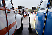 two classic Citroen 2CV cars watching people dance