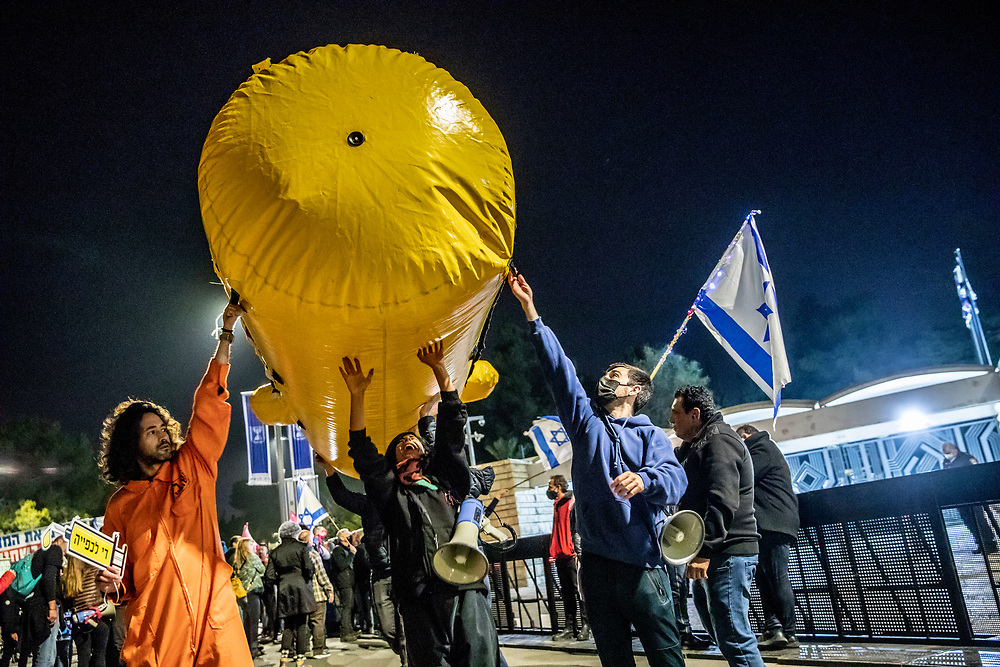 Anti-Netanyahu protesters hold a mock sub-marine as they demonstrate in front of the Israeli Presidential Residence , Israel, April 03, 2021. Several dozens marched from the formal Prime Minister residence to the Presidential residence in the Israeli capital. The Evidence stage of Israeli Prime Minister Benjamin Netanyahu's trial will begin April 5, 2021. The PM is charged by the Israeli State Attorney's Office with sections of fraud, bribery, and breach of trust.