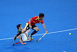 Pau Quemada of Spain evades the tackle of Lloyd Madsen of South Africa  during Pool MA Hockey  match between South Africa and Spain held at the Riverbank Arena in Olympic Park in London as part of the London 2012 Olympics on the 3rd August 2012..Photo by Ron Gaunt/SPORTZPICS