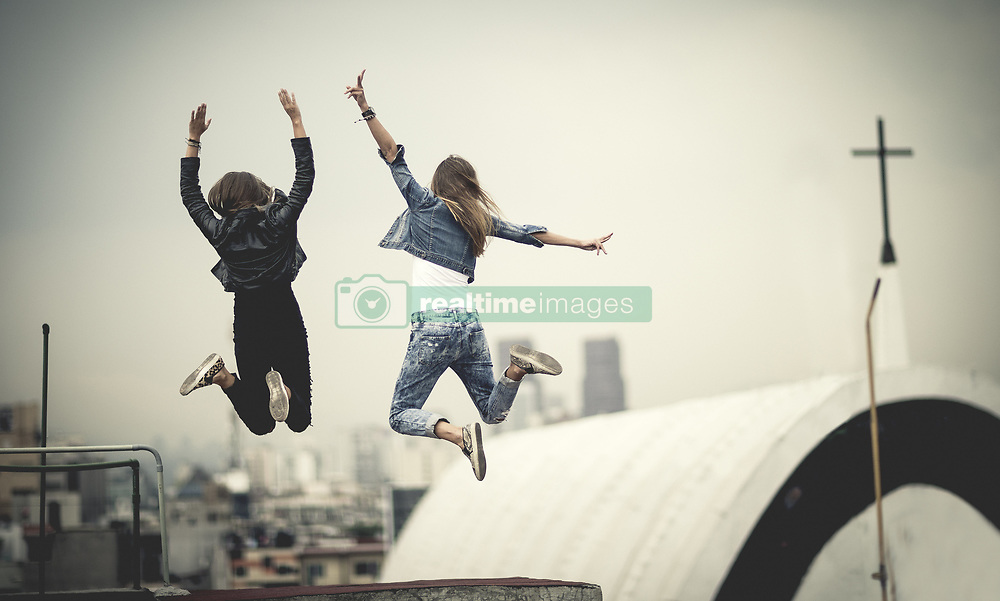 May 20, 2015 - Two young women standing on a rooftop with their arms raised. (Credit Image: © Mint Images via ZUMA Wire)