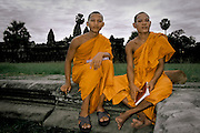 Monks rest and read in front of Angkor Wat temple in the Angkor Archeological Park in Siem Riep. Cambodia. August 2002