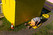 A man uses his bodyweight to deflate a large paddle board behind a bright yellow beach hut on the seafront promenade at Whitstable, on 18th July 2020, in Whitstable, Kent, England.