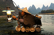 Cormorant fisherman lights his paraffin lamp ready for some night fishing on the Li River with his cormorants. The cormorants dive into the river from his bamboo raft and grab the fish in their beaks.They cannot swallow the fish as their throats are fitted with a tourniquet.Guanxi province, China
