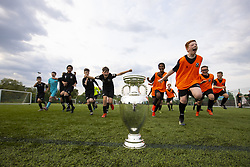 Handout photo dated 02/06/2021 provided by JSHPIX of Youngsters from Pollok FC juniors running by the Euro 2020 trophy as the Henri Delaunay Cup made a special visit to Glasgow today as part of the UEFA EURO 2020 Trophy Tour. Issue date: Wednesday June 2, 2021.