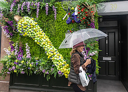 Licensed to London News Pictures. 27/06/2021. London, UK. A member of the public with an umbrella walks past a tennis themed floral decoration shop front in Wimbledon Village, southwest London ahead of the 2021 Championships which is set to kick off this Monday as weather forecasters predict thunderstorms and showers for the first 3 days. The AELTC Tennis Championships at Wimbledon is back on Monday (28 June) for the first time in two years after it was cancelled last year due to the Covid-19 pandemic. However, capacity is down by 50% and fans must pre-ordered tickets with no overnight camping or queuing. Photo credit: Alex Lentati/LNP