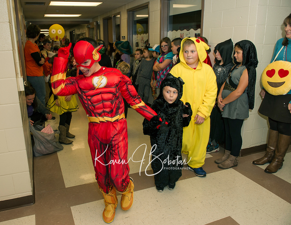 """Caden Tucker  """"Flash"""" leads his group through the halls at Pleasant Street School during the Halloween Parade on Friday afternoon.  (Karen Bobotas/for the Laconia Daily Sun)"""