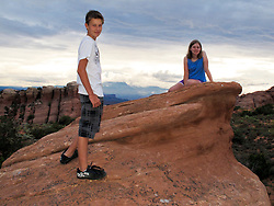 North America, United States, Utah, Arches National Park, boy (age 12) and girl (age 10) on rock.  MR