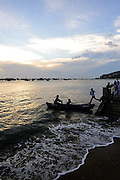 A man jumping from the sea-wall to a small boat, at sunset. Bai Truoc (Front Beach, aka Tam Duong beach), Hang Dua bay, Vung Tau, Vietnam