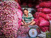 08 JANUARY 2013 - BANGKOK, THAILAND:   An onion and shallot vendor sorts his merchandise in the produce section of the Bangkok Flower Market. The Bangkok Flower Market (Pak Klong Talad) is the biggest wholesale and retail fresh flower market in Bangkok. It is also one of the largest fresh fruit and produce markets in the city. The market is located in the old part of the city, south of Wat Po (Temple of the Reclining Buddha) and the Grand Palace.    PHOTO BY JACK KURTZ