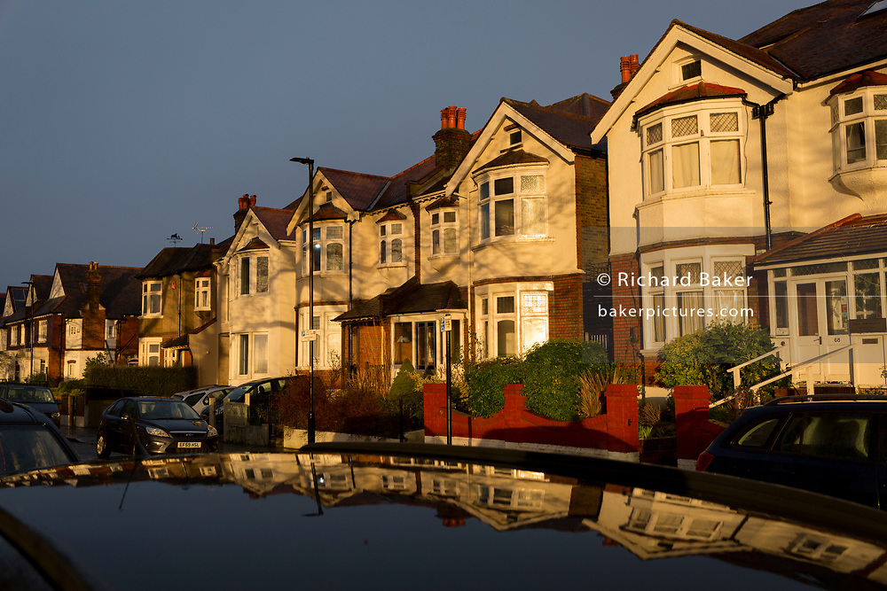 Reflected in a car's roof, are dark skies and brief sunlight on south London residential Edwardian period homes after heavy rainfall, on 25th February 2020, in London, England.