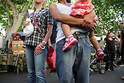 two females one hold a little child at an outdoor farmers market