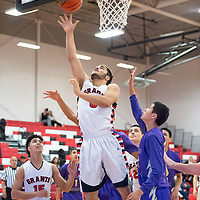 Adrian Ortega (5) scores after securing the offensive rebound against Kirtland Central at the Eddie Pena Classic in Grants on Saturday. Grants won 60-42.
