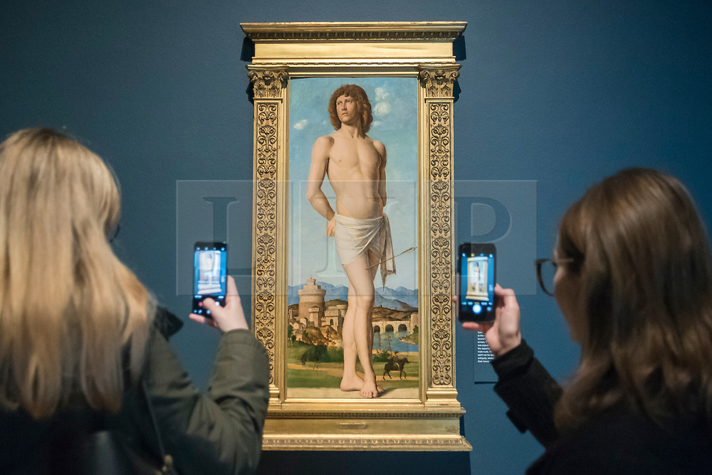 """© Licensed to London News Pictures. 28/02/2019. LONDON, UK. Visitors view """"Saint Sebastian"""" c1500-02 by Cima da Conegliano. Preview of """"The Renaissance Nude"""", an exhibition at the Royal Academy of Arts in Piccadilly of 90 works examining the emergence of the nude in European art.  Works by artists including Leonardo da Vinci to Michelangelo are on display in the Sackler Galleries 3 March to 2 June 2019.  Photo credit: Stephen Chung/LNP"""