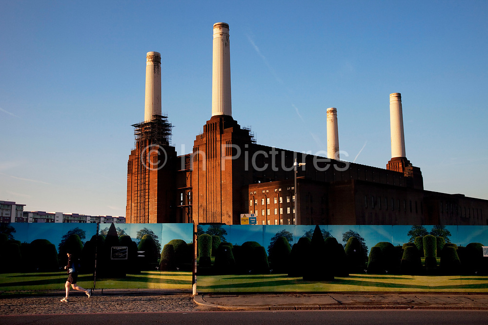 Jogger runs past the iconic Art Deco Battersea Power Station with it's distinctive four towers. Battersea Power Station is a decommissioned coal-fired power station located on the south bank of the River Thames, in Battersea, South London. The station comprises two individual power stations, built in two stages in the form of a single building. Battersea A Power Station was built first in the 1930s, with Battersea B Power Station to its east in the 1950s. The two stations were built to an identical design, providing the well known four-chimney layout. The station ceased generating electricity in 1983, but over the past 50 years it has become one of the best known landmarks in London and is Grade II listed.