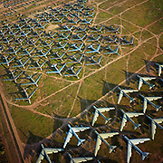 Seen from the air at dawn, the last remaining B-52 bombers from the Cold War-era are laid out in grids across the arid desert near Tucson Arizona. These retired aircraft whose air frames are too old for flight are being recycled, their aluminium worth more than their sum total. In the nuclear arms treaties of the 80s, Soviet satellites proved their decommissioning by spying the tails had been sliced apart huge guillotines and set at right-angles. This is a scene of confrontation, with opposing forces apparently facing each other in the way that Soviet and western armies fought the war of propaganda. Picture from the 'Plane Pictures' project, a celebration of aviation aesthetics and flying culture, 100 years after the Wright brothers first 12 seconds/120 feet powered flight at Kitty Hawk,1903.