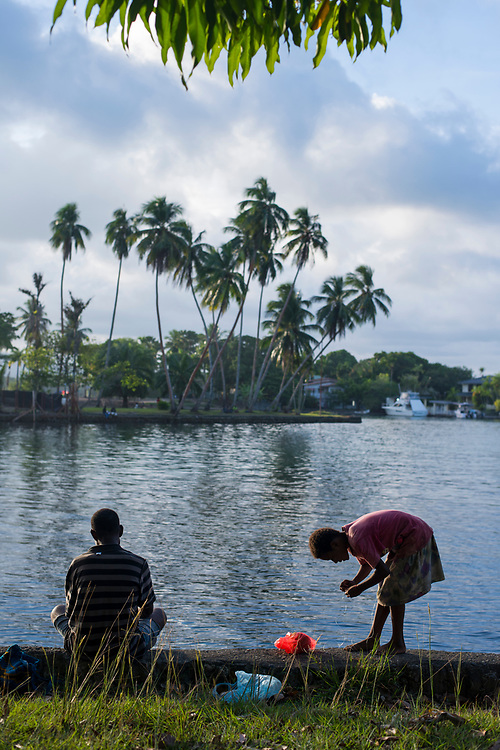 Late in the afternoon, a man and young girl fish with a spool of fishing line in the tranquil coastal waters in Madang, Papua New Guinea. The girl is putting bait on the fishing hook.